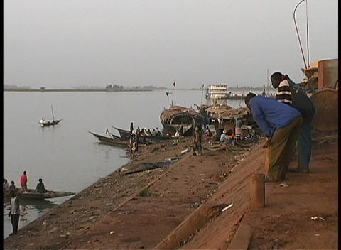 A medium-shot of longboats and people along the shores of the Niger River Footage
