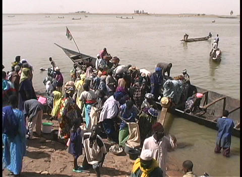 A birds-eye view of passengers leaving a long ferry boat on the muddy shores of the Niger River Footage