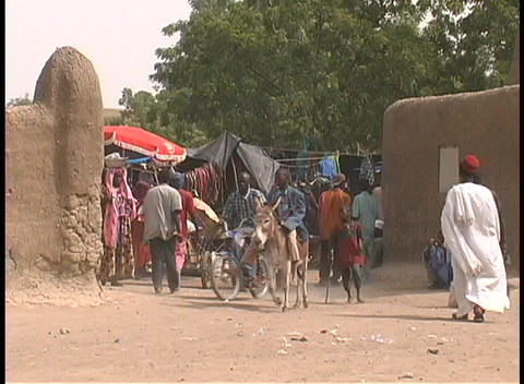 People of all ages, some in native dress, come and go from the open market in the village of Djenne Footage