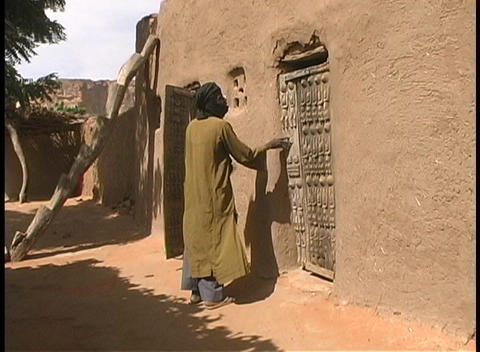 Man in traditional robes and turban struggles in the wind to close an old wooden door that is built Footage