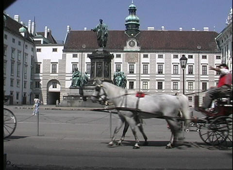 A medium shot of horse drawn carriages driving past a... Stock Video Footage
