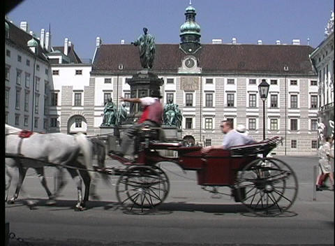 A medium shot of horse drawn carriages driving past a courtyard and sculpture in Vienna, Austria Footage