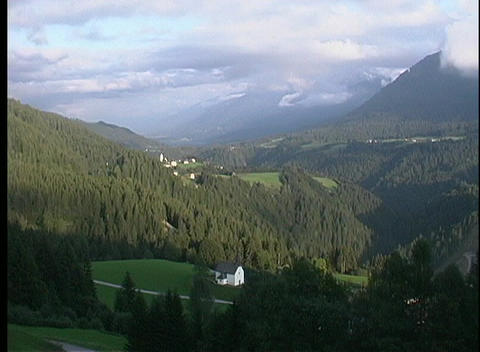 A mountain village and tree-lined valley lie under a... Stock Video Footage