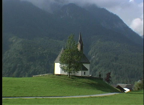 A small white church stands on a hilltop in an Austrian forest Footage
