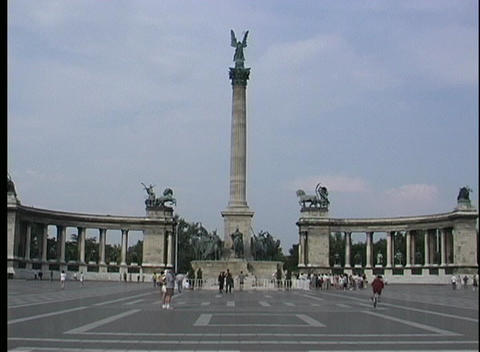 A medium-shot of tourists walking near Heroes' Square in Budapest, Hungary Footage