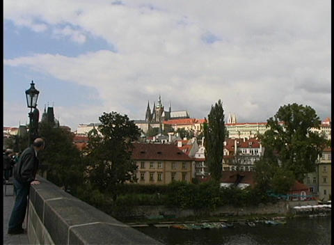 Tourists sightsee in Prague along a road that overlooks the city Footage