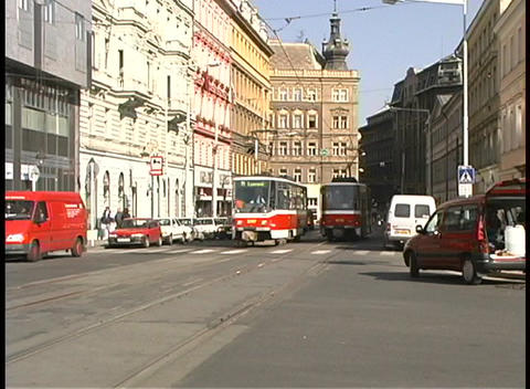 A medium-shot of streetcars and traffic on a city street in Prague Footage