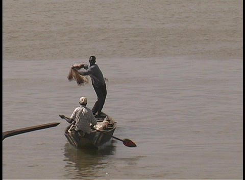 A fisherman casts his net from a boat in Mali, Africa Stock Video Footage