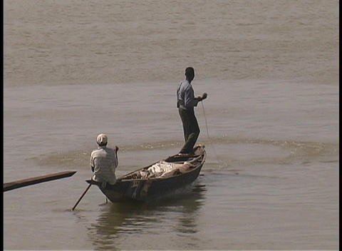 A fisherman casts his net from a boat in Mali, Africa Footage