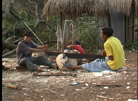 men in Thailand saw a log as a girl and young man watch... Stock Video Footage