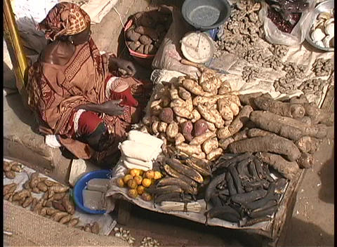 A vendor sells produce at an open market in Africa Live Action