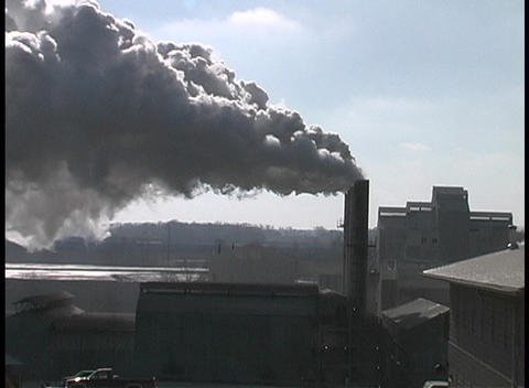 A factory pollutes the sky during golden hour Stock Video Footage
