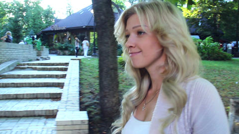 Blonde pretty woman walking in park follow camera, smiling, shy Footage