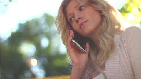 Dialing and calling phone young blond in park daytime, no answer Footage