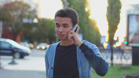 Black haired male calling phone talking in park hangs up smiling Footage