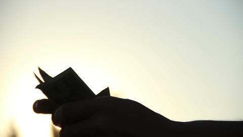 Counting and folding stack of money shot at dusk, male hands Footage