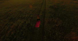 Aerial: camera tilt up over young woman doing yoga in a field at sunset Footage