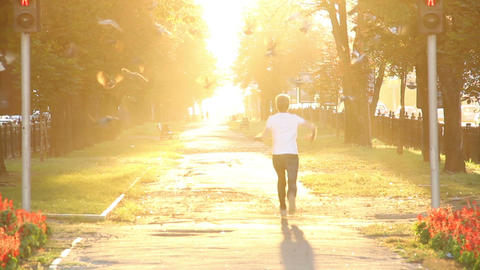 Jumping man in heavenly looking city boulevard sun shines bright Footage