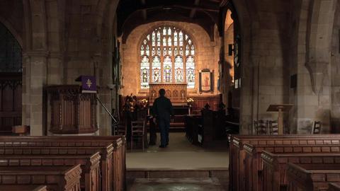Ely England man walks inside ancient church window 4K Live Action
