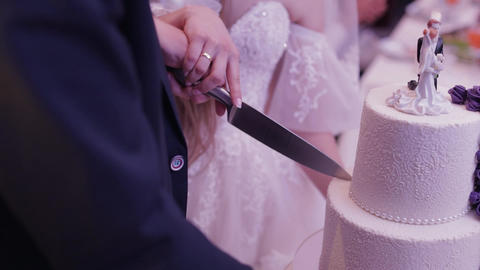 Bride and groom is cutting their wedding cake. Hands cut of a slice of a cake Live Action