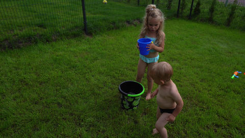 Cute blond sister girl pour water on her little brother boy from toy bucket Live Action