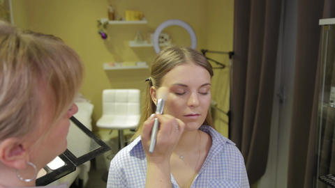 Professional makeup artist applying makeup brush to client Live Action