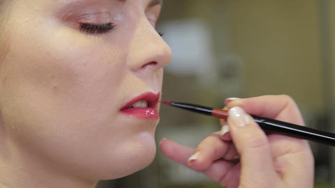 Professional make-up artist applying lip gloss on client s lips with a brush Live Action