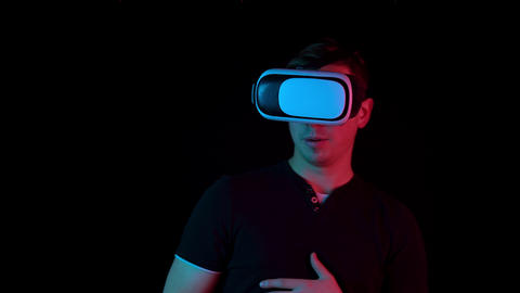 Young man in VR glasses. A man immersed in virtual reality makes movements with Live Action