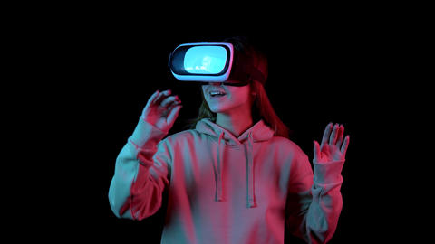 Young woman in VR glasses. A woman immersed in virtual reality makes movements Live Action