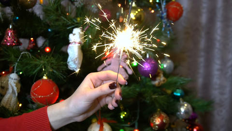 A girl holds a sparkler against the background of the Christmas tree slow Live Action