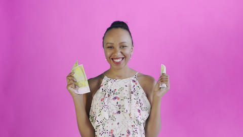 Attractive Afro american woman is counting money against a pink background Live Action