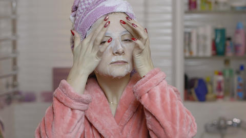 Woman applying cosmetic face mask in bathroom. Skincare spa. Facial mask Live Action