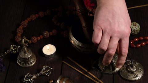 male hand arranges religious items of prayers and meditations Acción en vivo