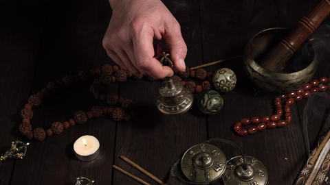male hand holds a bronze ritual bell for prayers and meditations, on a brown wooden table items Acción en vivo
