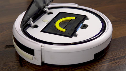 A dirty filter is pulled out of a vacuum cleaner robot. Automatic white round Live Action