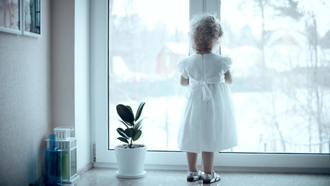 Curly blonde baby girl in white dress looks at falling snow through the window Live Action