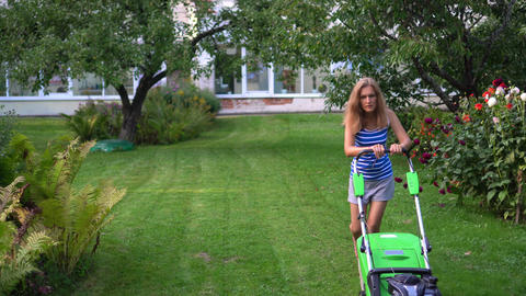 Young blond woman mowing lawn in residential back garden on summer evening Live Action