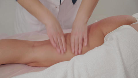 Woman massage therapist does massage on the legs of a young girl in a massage Live Action