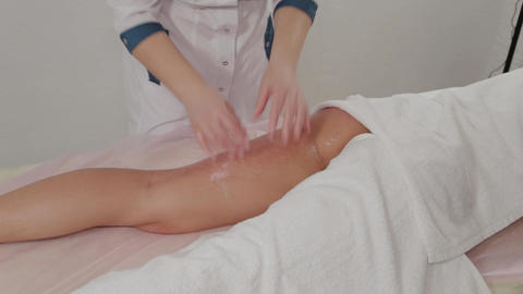 Woman massage therapist makes honey massage to a young girl in a massage parlor Live Action