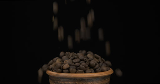 Whole beans of coffee fall on a bunch of beans lying in a clay pot and fall out Live Action