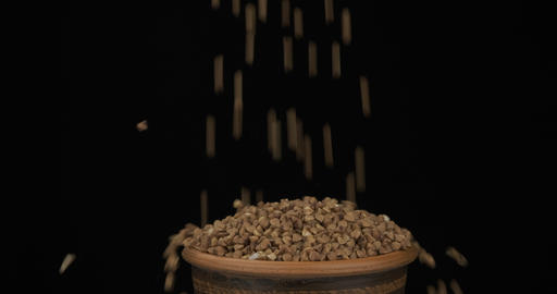 Whole grains of buckwheat fall on a bunch of grains lying in a clay pot and fall Live Action
