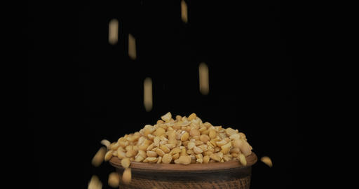 Whole grains of dry peas fall on a bunch of grains lying in a clay pot and fall Live Action