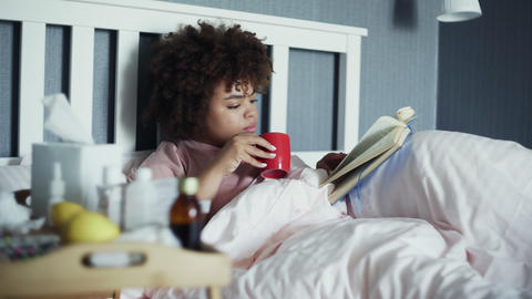 Sick african american girl has a cold at home. Lying in bed with a book and cup Live Action