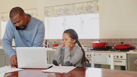 Father talking on mobile phone while daughter sitting beside in kitchen 4k Live Action