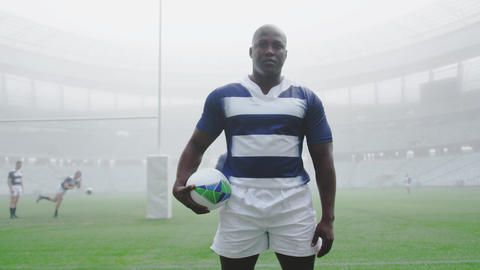 Rugby player standing with rugby ball in the stadium 4k Live Action