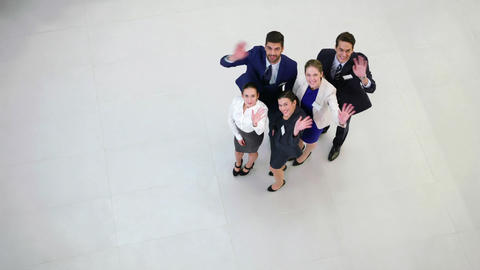 Smiling businesspeople waving hands in office Live Action