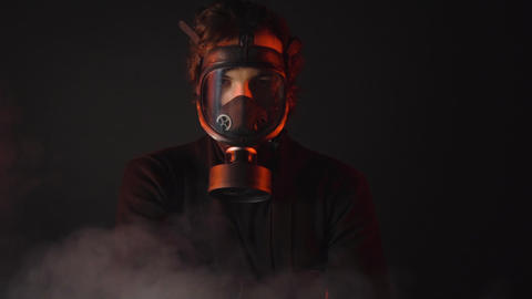 A man in black clothes with gas mask in toxic smoke on dark background Live Action