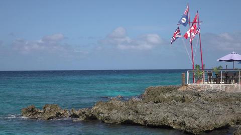 Grand Cayman Island Caribbean flags on beautiful shore 4K Footage