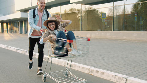Portrait of girl and guy having fun in city riding shopping trolley laughing Live Action