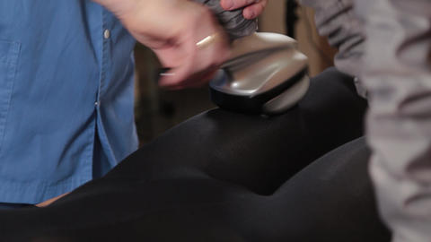 Professional male masseur makes a vacuum massage with a special device to a Live Action